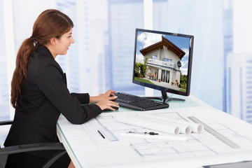 Female Architect Surfing House On Computer At Desk