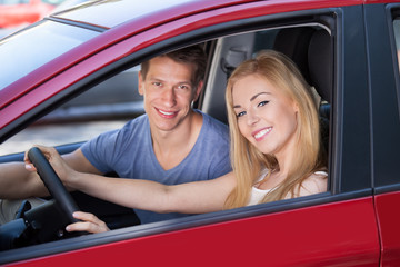 Happy Woman With Man Sitting In New Car