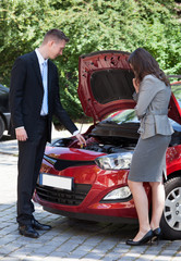 Salesman Showing New Car Engine To Female Customer
