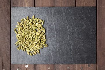 Cardamom seeds on a slate plate with copy space