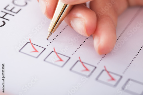 Leinwanddruck Bild Businesswoman Writing On Checklist