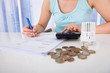 Woman Calculating Invoice By Coins And Thermostat At Desk