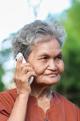 Asian old woman talking on mobile phone.