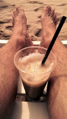 Male feet and plastic glass of cappuccino on a beach