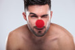 young naked man with red nose winking