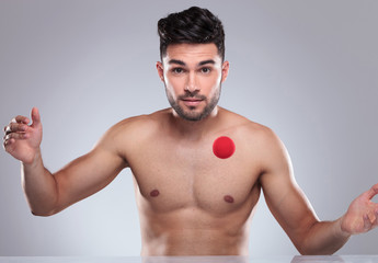 sexy naked young man playing with a red ball