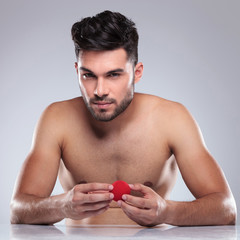 naked young man holding a red ball