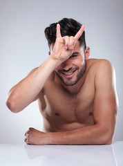 naked man making a rock and roll hand sign