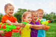 Kids play with water guns on a meadow - 67698745