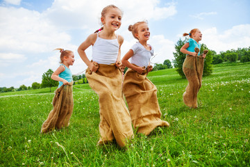 Kids having fun with sacks on a meadow