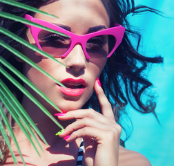 Young attractive woman wearing sunglasses under a palm tree