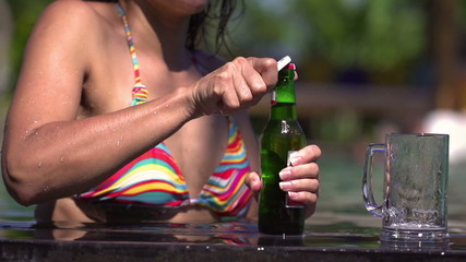 Woman open beer in pool, steadycam shot, slow motion shot