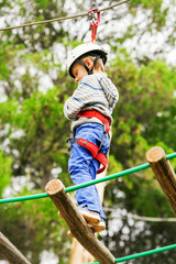 Boy in safe equipment on the rope-ladder in adrenalin park