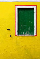 A yellow wall with a wooden green window surrounded by a frame