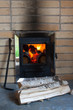 Leinwanddruck Bild - The wood stove with firewood and poker