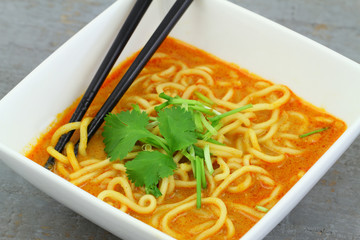 Hot curry noodles soup in bowl, close up