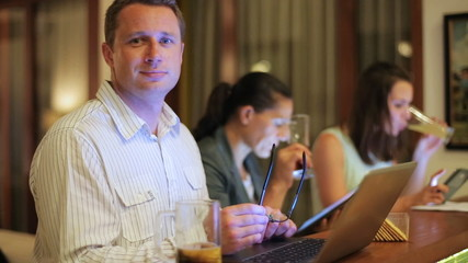 Man working on laptop and smiling to the camera in pub at night