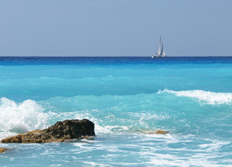 sea ​​waves and sailing boat in the background