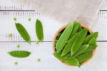 pods of green peas on a wooden background