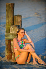 Young fashion pretty blond sexy woman relaxing on the beach.