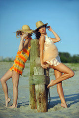 Two beautiful fashion models enjoy the beach.