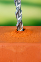 Close-up image of drilling hole on brick, on bright background