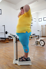impressed overweight woman on scales in gym