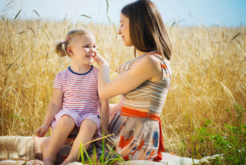 Young mother with cute daughter at wheat field