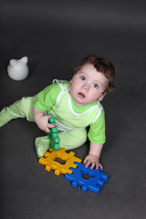 Baby in green crawlers sitting on floor with toys