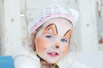 Little beautiful girl with face painting of orange fox poses