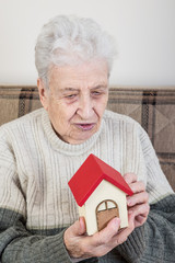 a senior person holding a small house