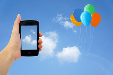Cell phone in hand take photo of beautiful balloon and sky view