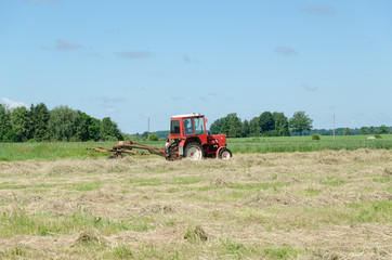 tractor machine equipment ted dry grass in field