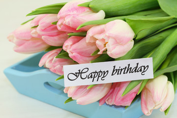 Happy birthday card with pink tulips on blue wooden tray