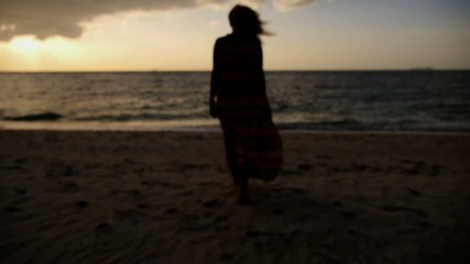 Pretty Woman Walking at Sunset on the Beach. Slow Motion.