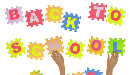"Hands forming phrase ""Back to school"" with jigsaw puzzle"