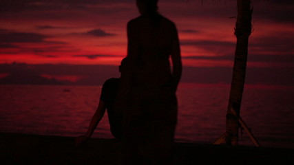 Couple talking and looking at beautiful sunset in exotic place