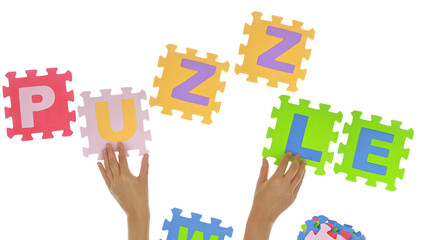 "Hands forming word ""Puzzle"" with jigsaw puzzle pieces isolated"
