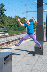 Handsome young guy jumping on train station