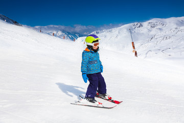 Small boy in ski mask and helmet skiing