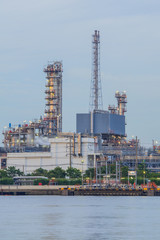 Close up oil refinery plant along the river before sunse