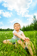 Boy does gymnastics while sitting on a meadow