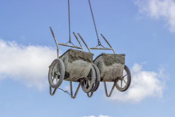 Crane lifting concrete wheelbarrow at constructoin site