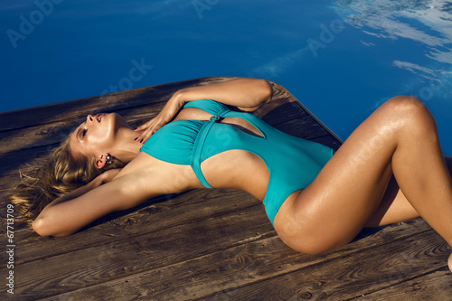 canvas print picture sexy girl in blue swimsuit relaxing beside a swimming pool
