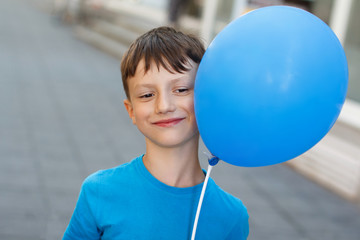 Happy little boy with blue air balloon