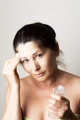 Asian woman clean face with lotion and cotton pad