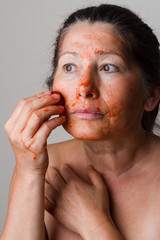Mature woman making cosmetic mask from strawberry.
