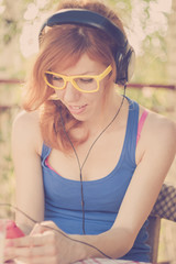 Beautiful hipster girl with big headphones listening to the musi