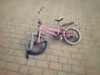 Broken pink bicycle lying on the street
