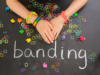 childs arm with loom band bracelets on a blackboard with elastic